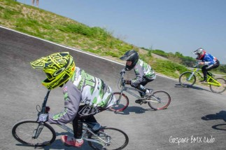 SK Racing team members scrap for best position entering the last berm at the National standard Gosport BMX track on the edge of the Alver Valley