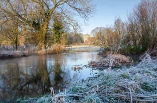 Frost covered banks ot the River Meon with St Mary and All Saints Church in the distance