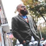 Photo of Owen Mathias. Bearded photographer wearing superman shirt standing in street