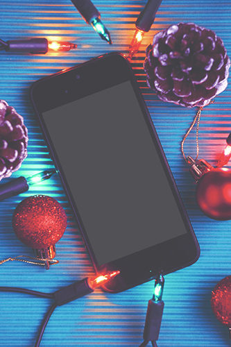 Smart phone and christmas decoration over blue background.