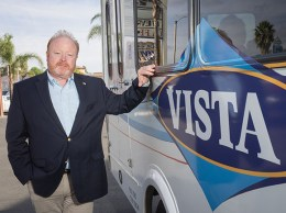 Chap Morris, owner of bus service Fillmore Area Transit Corp., stands alongside one of the company's buses. After 40 years in business, the firm will shutter by February. (Nik Blaskovich / Business Times photo)