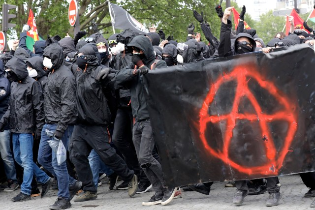 Protestors dressed in black and with the face covered, hold a banner picturing the symbol of the Anarchist as they take part in a march for the annual May Day workers' rally, in Paris, on May 1, 2018. / AFP PHOTO / Thomas SAMSON