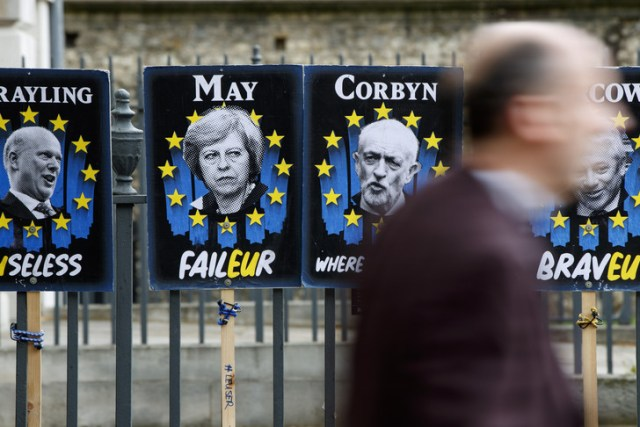 Pedestrians walk past placards featuring Britain's Prime Minister Theresa May and opposition Labour party leader Jeremy Corbyn near the Houses of Parliament in central London on April 3, 2019. - Prime Minister Theresa May was to meet on Wednesday with the leader of Britain's main opposition party in a bid to thrash out a Brexit compromise with just days to go until the deadline for leaving the bloc. (Photo by Tolga Akmen / various sources / AFP)