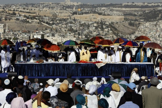 Israeli 'Kessim' or religious leaders of the Ethiopian Jewish community lead the prayers during the Sigd holiday marking the desire to 'return to Jerusalem', as they celebrate from a hilltop in the holy city over looking the Temple Mount, on November 16, 2017. Sigd used to mark the aspirations of Ethiopian Jews to go to Jerusalem and  nowadays the festivity is celebrated in Jerusalem with thousands of Ethiopians from all over Israel congregating to pray together, led by their religious leaders, the 'Kessim' who recites prayers while they overlook the old city of Jerusalem. / AFP PHOTO / GALI TIBBON