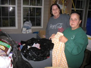 Denise Snyder and Marilyn Saville packing clothes for Rivere Mancelle