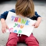 child holding thank you god sign