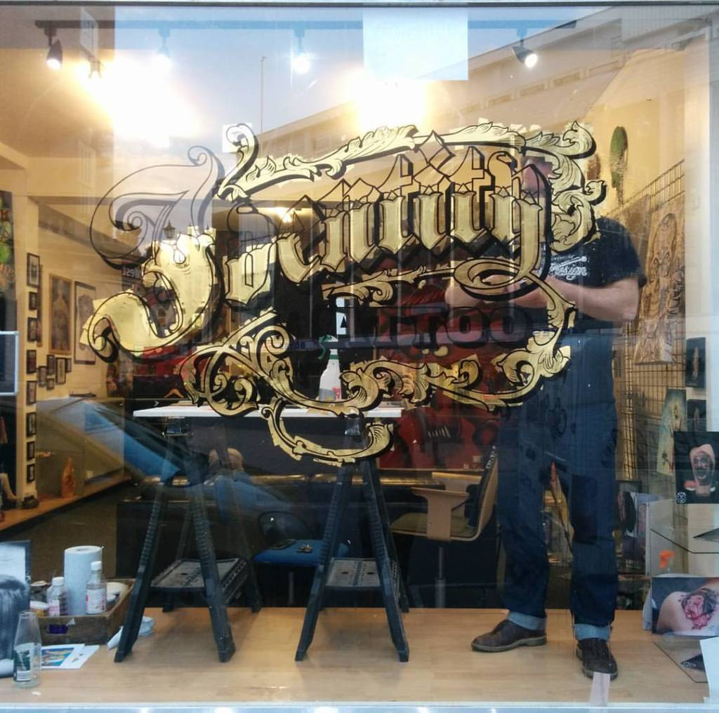 Sign Writer working on a tattoo studio gold leaf sign