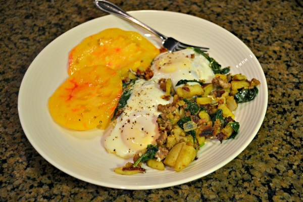 hash with potatoes, spinach, onions and Italian sausage. served with two eggs and sliced tomatoes