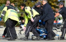 Paramedics and police pull a shooting victim away from the Canadian War Memorial in Ottawa on Wednesday Oct.22, 2014. (Photo: AP)