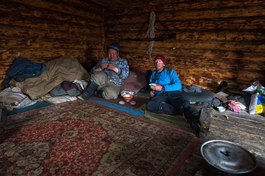 A Mongolian herder rolls a cigarette in newsprint while Forrest McCarthy sips a salty-milk Suutei Tsai tea.