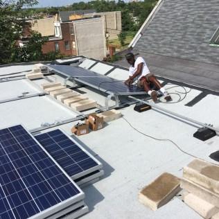 Robert installing panels on roof