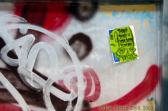 Grafitti and sticker in window of a failed store on the Lower East Side