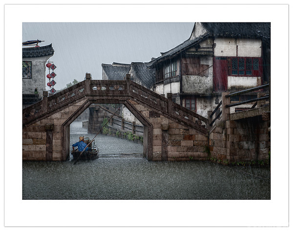 A boatman takes shelter from the torrential rain in Xitang, Zhejiang, China (Ian Mylam/© Ian Mylam (www.ianmylam.com))