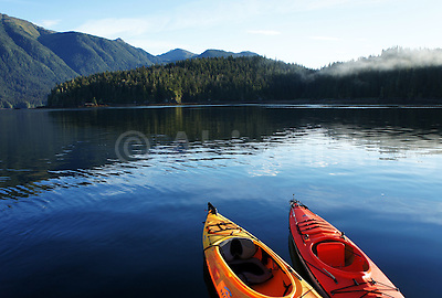 Photos from a kayak expedition to southeast Alaska. Featuring red and yellow kayaks against clear blue water, mountains and cloud-streaked skies. (Abigail King)