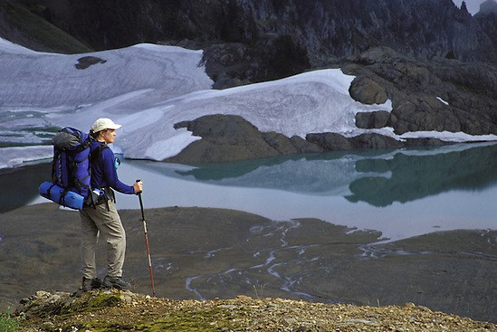 Backpacker overlooking alpine lake and meadows, North Cascade Mountains, Washington State