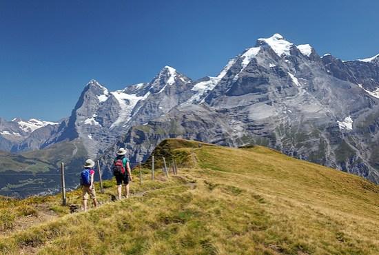 Woman and girl hiking on Wasenegg ridge on Schilthorn mountain, Eiger, Mönch and Jungfrau in background, Switzerland (Brad Mitchell)