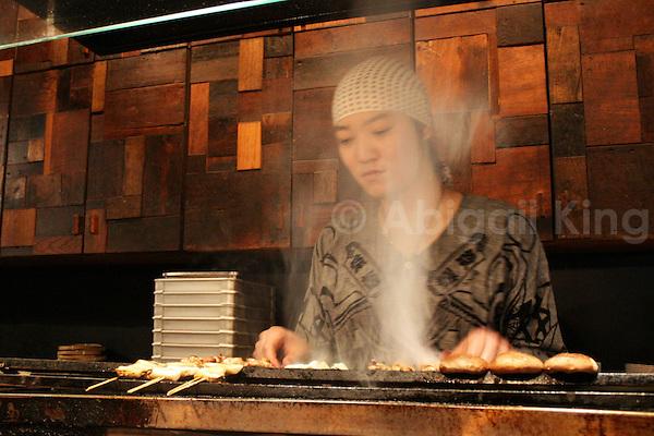 Food sizzling in a Yaketori bar in Tokyo