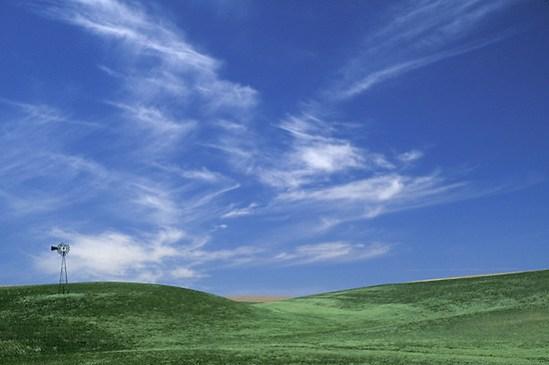 Windmill in wheat fields below blue sky with clouds, Palouse area, Washington
