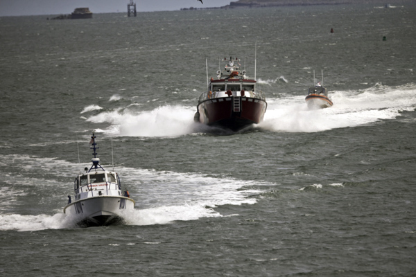 04/29/2016-Boston,MA. From left, The Boston Police Marine, a Boston Fire rescue boat, and a U.S. Coast Guard boat are seen after leaving the oil tanker Hugli Spirit, after a medical incident was reported on board, near the noon hour Friday. A person was taken off the ship and is in the Fire Rescue boat, the middle boat here. Staff Photo by Mark Garfinkel