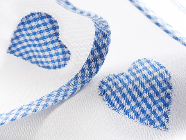 Blue gingham hearts applied to white cotton fabric.