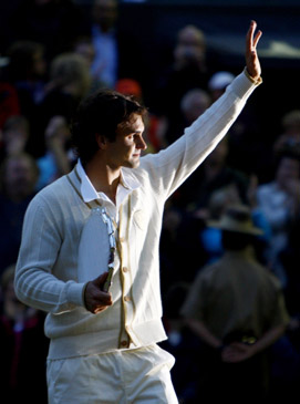 Roger Federer of Switzerland waves as he holds the runners up trophy after being defeated by Rafael Nadal of Spain at the Wimbledon tennis championships in London July 6, 2008.