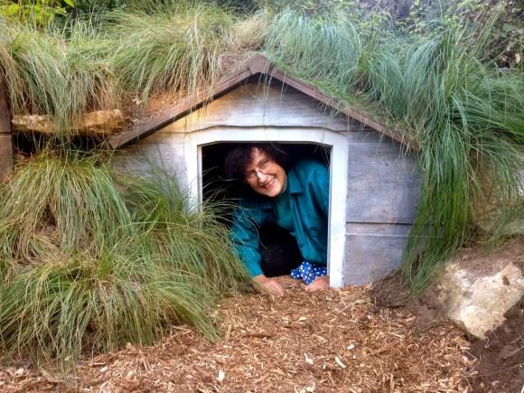 wine and weed volunteer plays in garden hobbit house at fernwood gardens