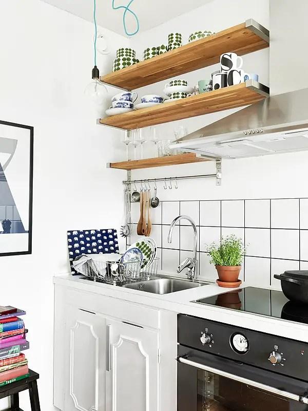 Pequena cozinha com armários embaixo e prateleiras em cima. As