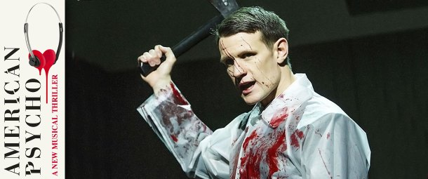 A scene from American Psycho the musical at the Almeida Theatre. The image shows Matt Smith in the lead role of Patrick Bateman who is wearing a white shirt splattered in blood. In his right hand, raised behind his head, he holds a black blood stained axe.