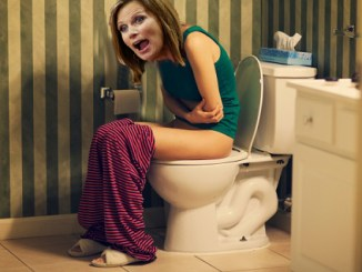 Woman in pain on toilet in bathroom
