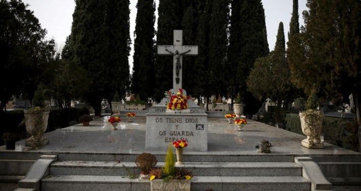"""A monument that reads """"God keeps you and Spain guards you"""" stands at Guadalajara's cemetery, Spain, January 19, 2016. Spanish campaigners dug up a mass grave on Tuesday in a search for victims of the country's civil war and the fascist dictatorship it put in place, as an Argentine court puts pressure on Spain to confront its troubled past. REUTERS/Juan Medina - RTX23427"""