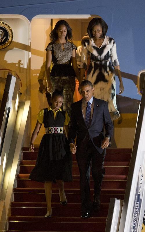 Los Obama aterrizan en Senegal. Tanto el vestido con el cinturón de la hija pequeña, como el estampado de la madre y la hija mayor son un guiño al país que los recibe.