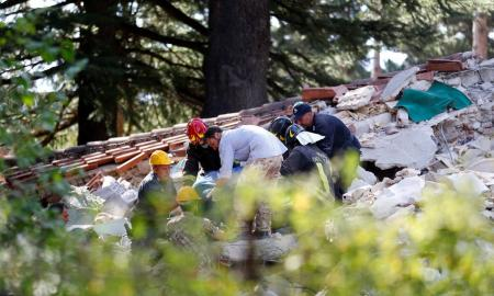 Rescuers work at a collapsed building following an earthquake in Amatrice, central Italy, August 24, 2016. REUTERS/Stefano Rellandini