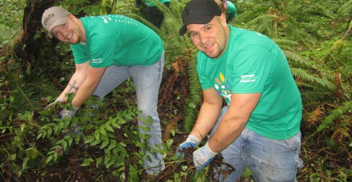 Comcast employees Alex Mcewan and Jesse Lambert remove invasive ivy at Tryon Creek State Park. Photo by Jayson Claypool.