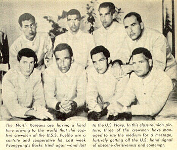 North Korean Propaganda Photograph of prisoners of USS Pueblo. Photo and explanation from the Time Magazine article that blew the Hawaiian Good Luck Sign secret. The soldiers were flipping the middle finger, as way to covertly protest their captivity in North Korea, and the propaganda on their treatment and guilt. The North Koreans for months photographed them without knowing the real meaning of flipping the middle finger, while the sailors explained that the sign meant good luck in Hawaii.
