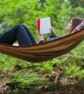 Pretty, mid-adult woman reading in hammock.