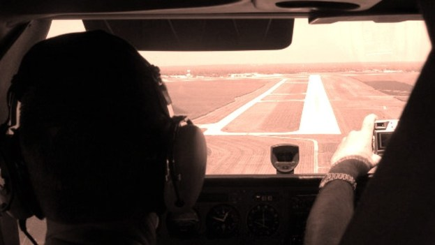 Pilots landing a small plane on a landing strip.