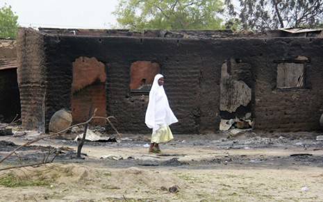 A woman walks past burnt houses in the aftermath of what Nigerian authorities said was heavy fighting between security forces and Islamist militants in Baga, a fishing town on the shores of Lake Chad, adjacent to the Chadian border, April 21, 2013. The bloody gun battle against Islamist insurgents in Nigeria last week involved forces from neighbouring Chad and Niger, officials said on Tuesday, as West African countries increasingly view jihadist groups as a cross-border threat. There was no confirmation of the death toll from Friday's fighting, but a Nigerian military source said dozens may have died, many of them civilians. The Nigerian Red Cross said it was checking reports from locals that 187 people had died, but had still not obtained security clearance to go into Baga. Picture taken April 21, 2013.   REUTERS