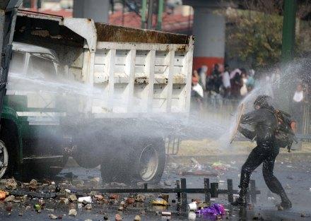 Un manifestante recibe un chorro de agua durante la toma de posesión de Peña en San Lázaro. Foto: Rubén Espinosa