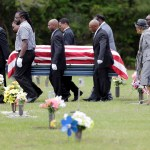 Photo courtesy of the Associated Press  Pallbearers walk Walter Scott's casket to the gravesite for his burial service in Charleston, S.C. on Saturday, April 11, 2015. Scott was fatally shot by a North Charleston, S.C., police officer a week earlier after a traffic stop. Officer Michael Slager has been charged with murder.