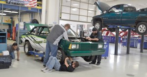 Photo by Lindsay Cox | Automotive tech students Zach Stamm (left) and AJ Ross (right) lean over the car they are working on for the upcoming car show, while Kyle Vanvleet sees to the repairs of the undercarriage and Amr Elgendy supervises from the back corner.