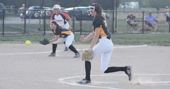 hoto by Tom Warner | Cobras pitcher Morgan Parrish pitches while third baseman Brigette Belt stands ready for action.
