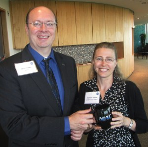 Stephanie Thomas and Jason Derleth posing with a NIAC mug