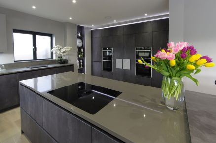 Concrete graphite kitchen with island and secret doors to utility room. Open decorative shelving