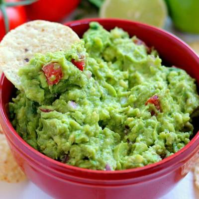 Filled with ripe avocados, fresh tomatoes, red onions, and spices, this Zesty Guacamole is jam-packed with flavor and ready to eat in just five minutes. It makes the perfect dip for chips, toppings for tacos and burritos, and spreads for sandwiches!