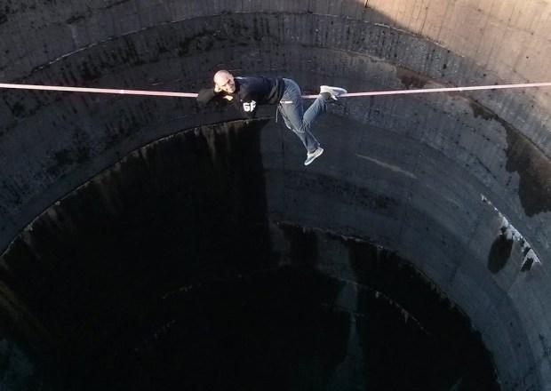 فيديو: رجل يسير فوق هاوية بعمق 60 متر وبدون أدوات السلامة !