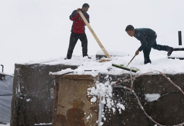 Syrian refugees remove snow from tents at a refugee camp during a wind storm in Zahle