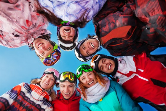 Seven happy laughing friends standing in circle wearing goggles on the skies background