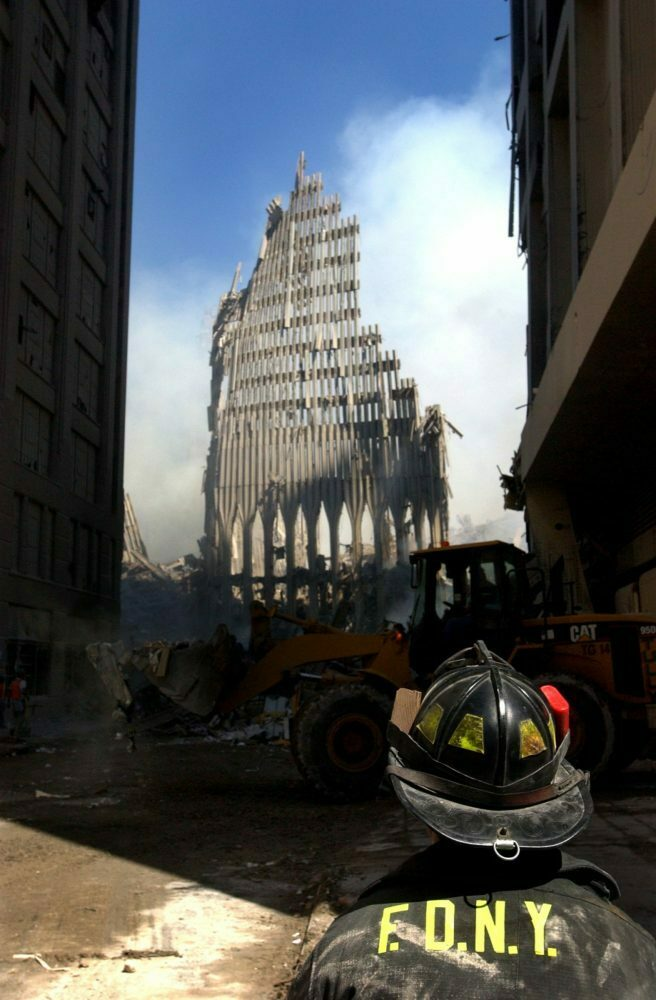 New York, N.Y. (Sept. 13, 2001) -- A New York City fire fighter looks up at what remains of the World Trade Center after its collapse following a Sept. 11 terrorist attack.  U.S. Navy Photo by Photographer's Mate 2nd Class Jim Watson.  (RELEASED)