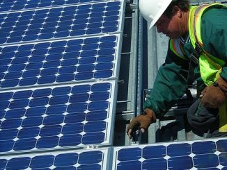 A construction worker installs solar panels on the sun shades in a motor pool at the Combat Center as part of an U.S. Marine Corps initiative to triple the amount of renewable energy the base uses.