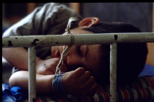 72628 018: A child sleeps with his hand tied to the bars at an orphanage May 16, 1990 in Ploiesti, Romania. The orphanage is for children who have birth defects such as retardedness and deformities. (Photo by Cynthia Johnson/Liaison)